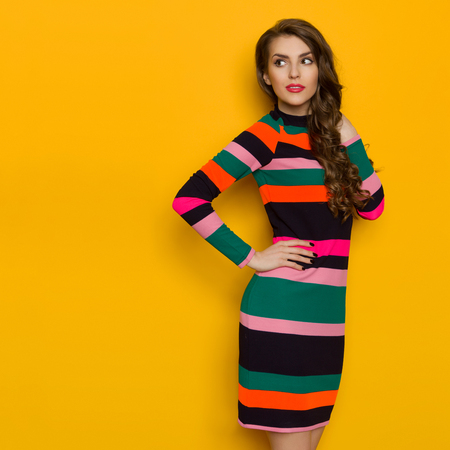 Beautiful young woman in colorful vibrant striped dress with long sleeves is standing with hand on hip, looking away over the shoulder. Three quarter length studio shot on yellow background. Stock Photo