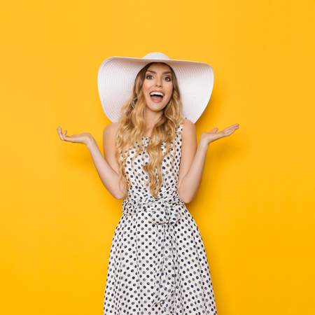Beautiful young woman in white dotted summer dress and sun hat is holding hand raised, presenting, looking at camera and shouting. Three quarter length studio shot on yellow background.