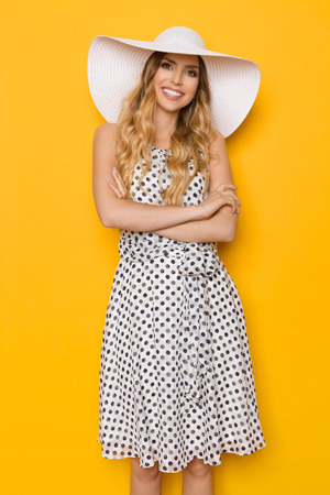 Beautiful young woman in white dotted summer dress and sun hat is standing with arms crossed, smiling and looking at camera. Three quarter length studio shot on yellow background.