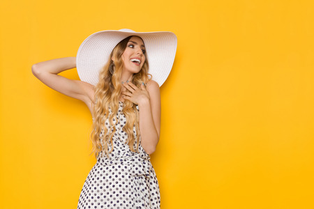 Beautiful young woman in white dotted summer dress and sun hat is holding hand on chest, looking away and smiling. Three quarter length studio shot on yellow background. Zdjęcie Seryjne