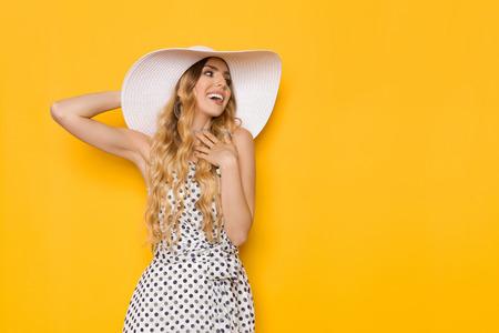 Belle jeune femme en robe d'été en pointillé blanc et chapeau de soleil se tient la main sur la poitrine, en détournant les yeux et en souriant. Studio de trois quarts tourné sur fond jaune.