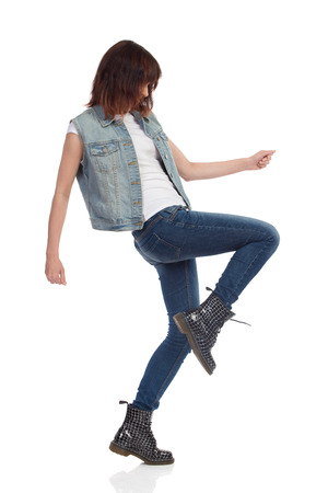 knee boots: Young woman in jeans vest and black boots is standing on one leg and dancing. Side view. Full length studio shot isolated on white.