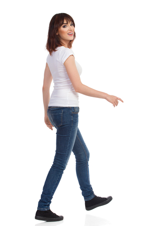 Young woman in jeans and white t-shirt is walking, looking at camera over the shoulder and talking. Full length studio shot isolated on white.