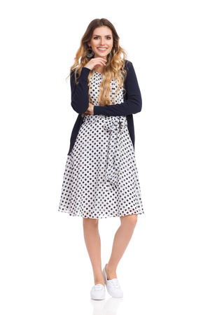 hapy: Beautiful young woman in white dotted summer dress and blue cardigan is standing, holding hand on chin, smiling and looking at camera. Full length studio shot isolated on white.