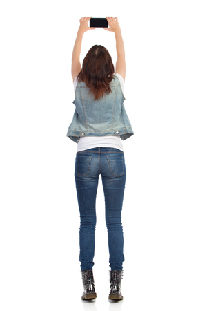 Rear view of young woman in jeans vest and black boots, standing and holding cell phone over her head and taking photo. Full length studio shot isolated on white.