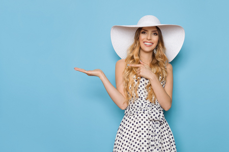 Beautiful young woman in white dotted summer dress and sun hat is standing with hand raised, presenting something, pointing and smiling. Three quarter length studio shot on turquoise background. Stock Photo