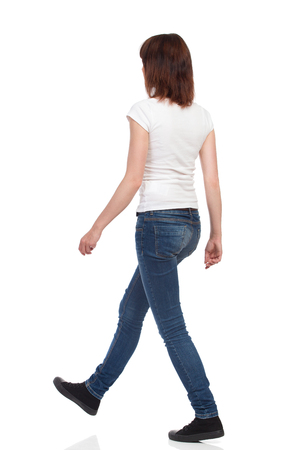 Young woman in jeans and white t-shirt is walking. Rear Side View. Full length studio shot isolated on white.