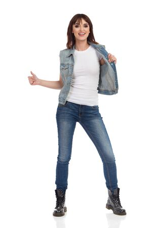 Happy young woman in jeans vest, black boots and brown suede hat is standing, smiling and showing thumb up. Full length studio shot isolated on white.