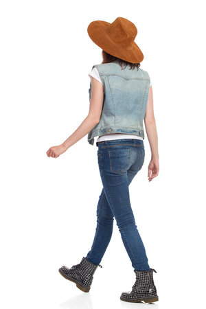 Young woman in jeans vest, black boots and brown suede hat is walking. Side rear view. Full length studio shot isolated on white.