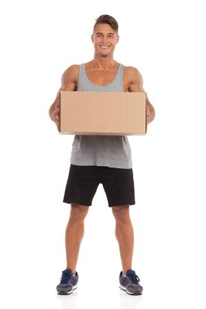 Young muscular man in black shorts, gray tank top and sneakers is standing, holding beige box and smiling. Full length studio shot isolated on white.