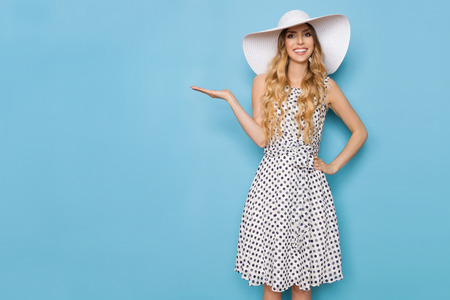 Beautiful young woman in white dotted summer dress and sun hat is standing with hand raised, presenting something and smiling. Three quarter length studio shot on turquoise background.