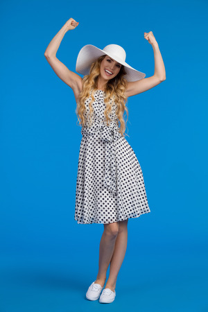 Beautiful young woman in white summer dress, sneakers and sun hat is laughing, holding arms raised and looking at camera. Full length studio shot on blue background.