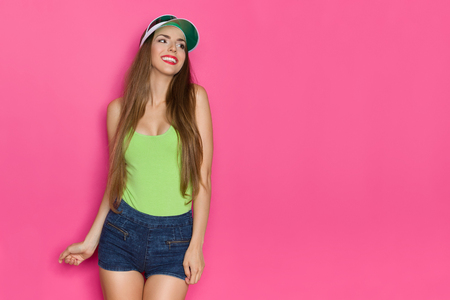 Smiling young woman in jeans shorts, lime green tank top and green sun cap is looking away. Three quarter length studio shot on pink background.