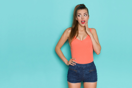 Surprised young woman in orange tank top is holding hand on chin and looking away. Three quarter length studio shot on turquoise background. Фото со стока