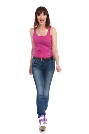 Happy young woman in jeans, magenta tank top and sneakers is walking towards camera and shouting. Front view. Full length studio shot isolated on white.