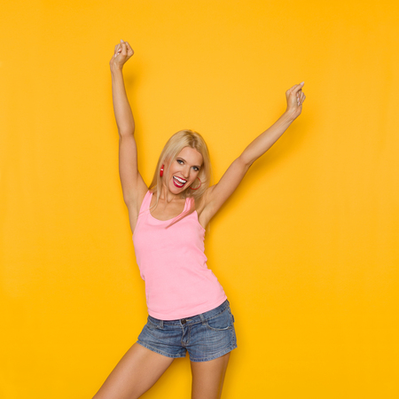 Beautiful blond woman in pink tank top and jeans shorts is standing with arms raised and shouting. Three quarter length studio shot on yellow background.
