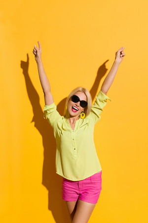 Happy beautiful blond woman in yellow shirt and pink shorts is standing with arms raised and shouting. Three quarter length studio shot on yellow background. Stock Photo