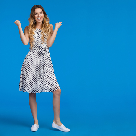 Beautiful young woman in white summer dress and sneakers, clenching fists, laughing and looking at camera. Full length studio shot on blue background.