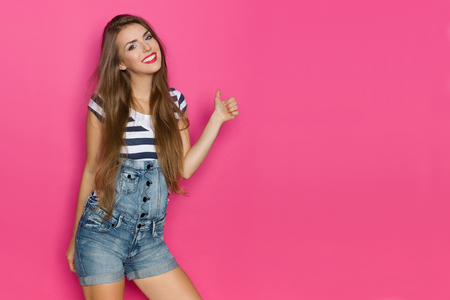 Beautiful young woman in dungarees shorts and blue striped shirt is smiling, showing thumb up and looking at camera. Three quarter length studio shot on pink background.