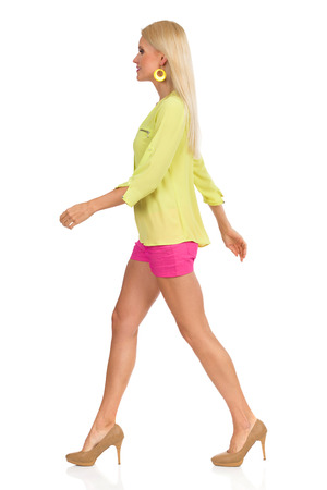 Beautiful blond woman in pink shorts, green shirt and high heels is walking and looking away. Side view. Full length studio shot isolated on white. Stock Photo