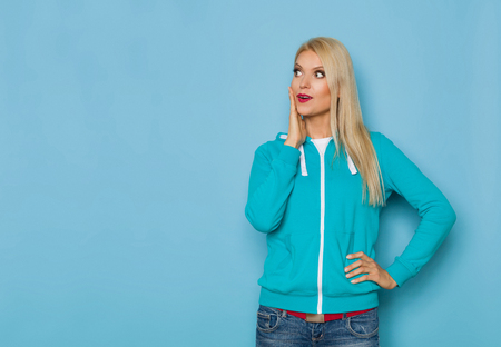 Beautiful blond woman in turquoise sweater and is holding hand on chin and looking away at copy space. Three quarter length studio shot on turquoise background.