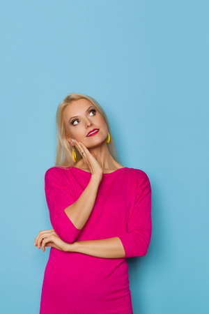 Beautiful blond woman in pink sweater is holding hand on chin, looking up and dreaming. Three quarter length studio shot on turquoise background.