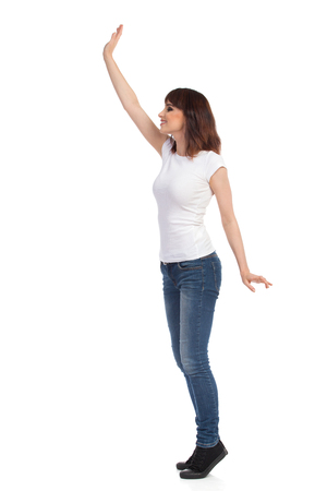 Happy young woman in jeans and white t-shirt is standing on tiptoes, rising arm, waving, looking away and smiling. Full length studio shot isolated on white.