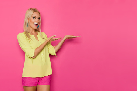 Happy beautiful blond woman in yellow shirt and pink shorts is standing with hands raised, looking at camera, talking and showing something. Three quarter length studio shot on yellow background.