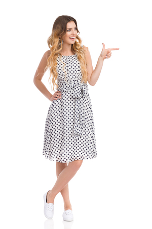 Beautiful young woman in white dotted dress and sneakers is standing, pointing, smiling and looking away. Front view. Full length studio shot isolated on white.