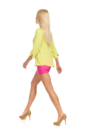 Beautiful blond woman in pink shorts, green shirt and high heels is walking and looking away. Rear side view. Full length studio shot isolated on white. Stock Photo