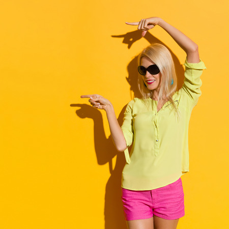 Smiling beautiful blond woman in yellow shirt and pink shorts is standing with arms raised, looking away and pointing. Three quarter length studio shot on yellow background.