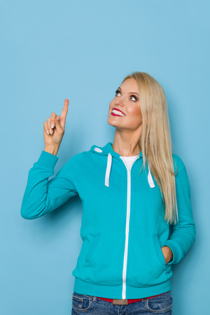 Smiling beautiful blond woman in turquoise hoodie is looking up and pointing. Three quarter length studio shot on turquoise background.