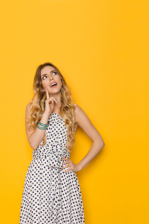 disbelief: Beautiful young woman in white dotted summer dress is holding finger on chin, looking up and thinking.Three quarter length studio shot on yellow background.