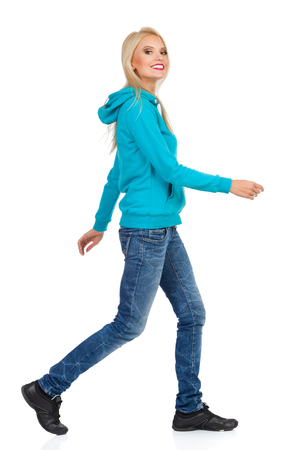 Beautiful blond woman in turquoise hoodie and jeans is walking, looking at camera and smiling. Full length studio shot isolated on white.