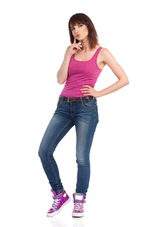 Young woman in jeans, magenta tank top and sneakers is standing, looking away and planning. Front view. Full length studio shot isolated on white.