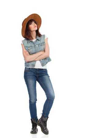 Beautiful young woman in jeans vest, brown suede hat and black boots is standing with arms crossed and looking up. Full length studio shot isolated on white.
