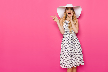 Beautiful young woman in white dotted summer dress and sun hat is holding hand on chin, shouting and looking at camera. Three quarter length studio shot on pink background.