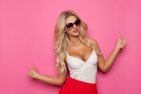 Beautiful blond woman in sunglasses, white corset and red trousers is showing thumbs up. Waist up studio shot on pink background.