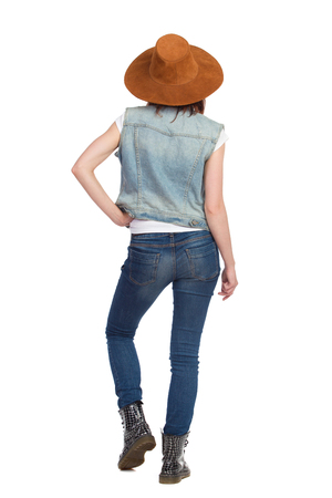 Young woman in jeans vest, black boots and brown suede hat is standing and holding hand on hip. Rear view. Full length studio shot isolated on white.