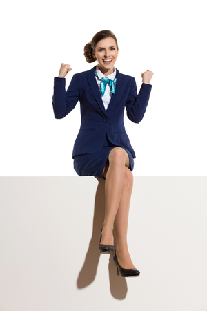 Elegant woman in blue suit and black high heels is sitting on a top with legs crossed, holding arms raised, smiling and looking at camera. Full length studio shot.