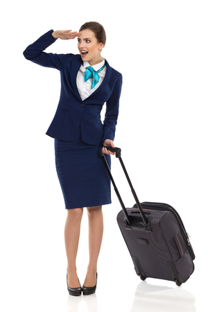 Ecstatic woman in blue suit and skirt is standing with trolley bag, holding hand on forehead, looking away and talking. Full length studio shot isolated on white. Stock Photo