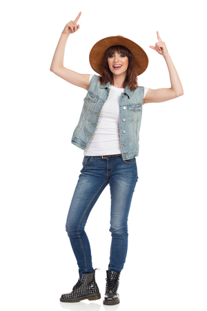 Happy young woman in jeans vest, black boots and brown suede hat is standing, looking at camera, pointing up and talking. Full length studio shot isolated on white. Stock Photo