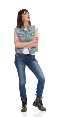 Beautiful young woman in jeans vest and black boots is standing with arms crossed and looking up and talking. Full length studio shot isolated on white. Stock Photo