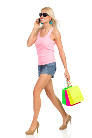 Beautiful blond woman in jeans shorts, pink tank top, and high heels is walking, holding shopping bags andtalking on the phone. Side view. Full length studio shot isolated on white.
