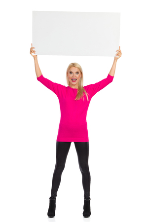 Beautiful blond woman in black leggings, high heels, pink sweater is standing, holding blank placard over her head and shouting. Full length studio shot isolated on white.