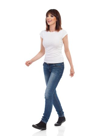 Young woman in jeans and white t-shirt is walking, looking away and talking. Full length studio shot isolated on white.