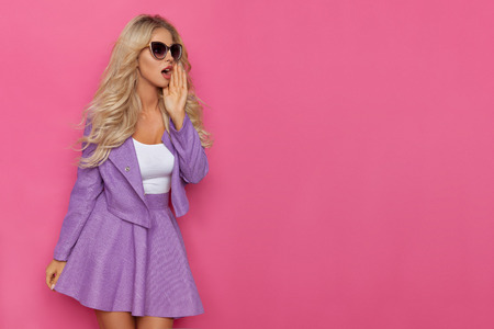 Beautiful blond woman in violet mini skirt, jacket and sunglasses is holding hand on chin, talking and looking away. Three quarter length studio shot on pink background.