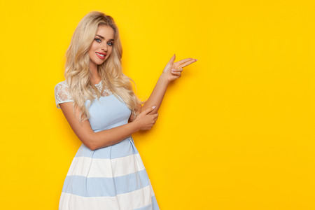 Blond beautiful woman in white and blue dress is looking at camera and pointing with pistol hand sign. Three quarter length studio shot on yellow background.