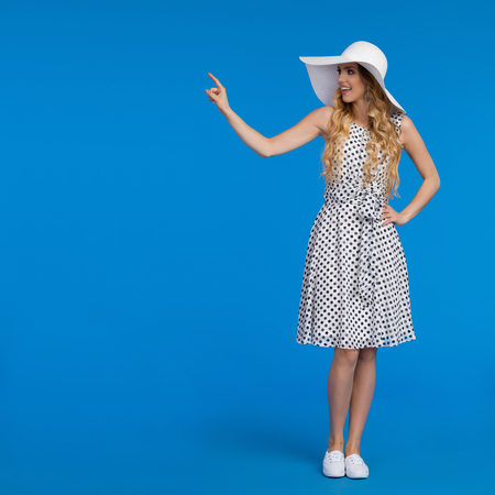Beautiful young woman in white summer dress, sneakers and sun hat is standing, touching something and looking away. Full length studio shot on blue background.
