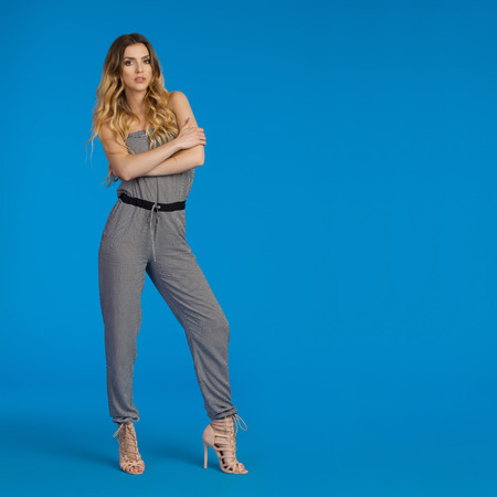 Beautiful young woman in dotted jumpsuit and high heels  is standing with arms crossed and looking at camera. Full length studio shot on blue background. Stock Photo